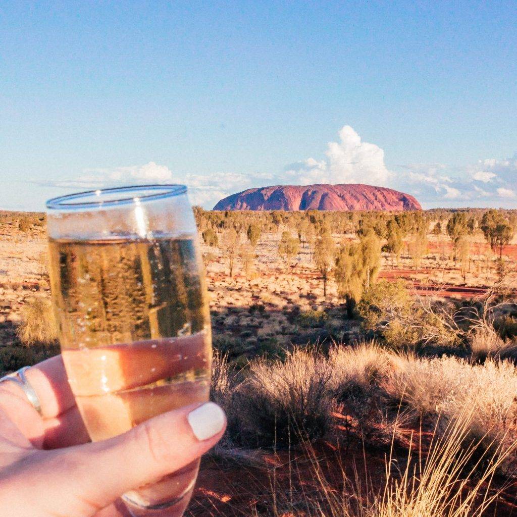 Raising a glass of champagne to Uluru in the distance at sunset
