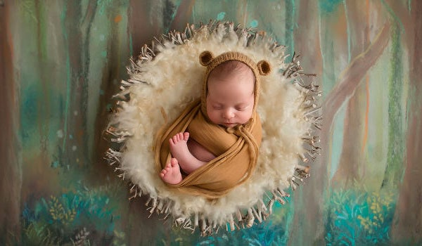 A sleeping baby dressed as a bear for a photography shoot