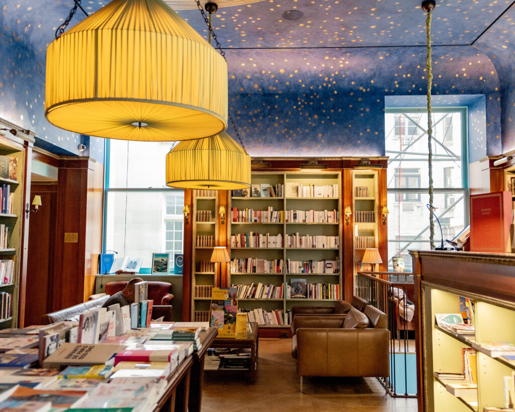A bookstore reading room with low hanging lights and starry ceiling