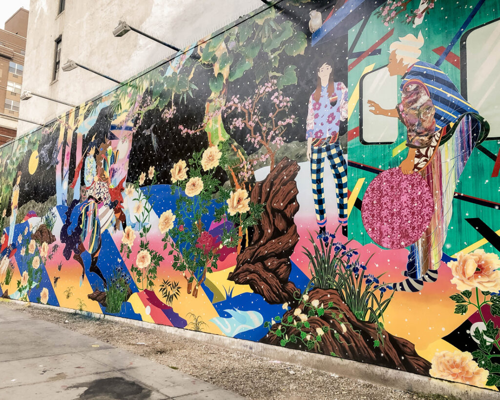 Large wall mural painted with florals and people in bright colours