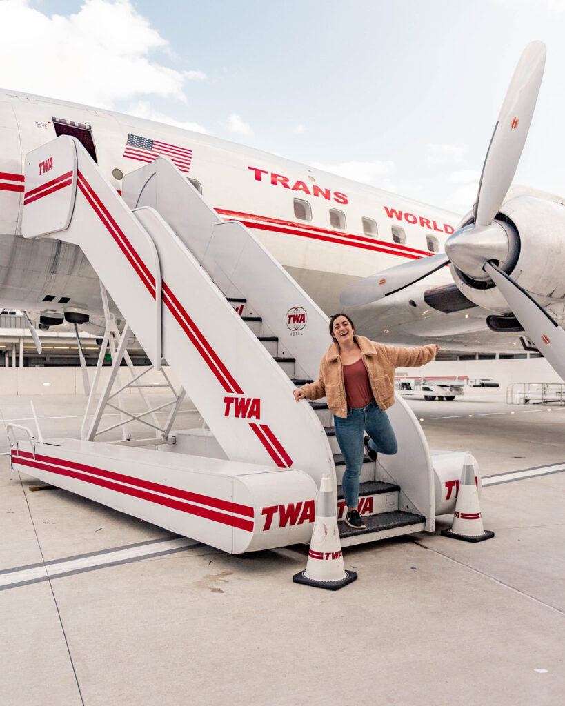 Girl coming down stairs that lead to a small, old TWA plane